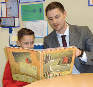 Head teacher reading to pupil